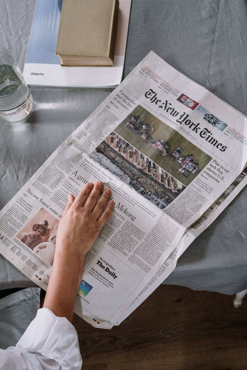 person reading newspaper on table